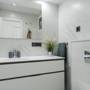 Modelo de aseo actual, de tamaño medio, con armarios con paneles lisos, puertas de armario grises, sanitario de pared, baldosas y/o azulejos grises, baldosas y/o azulejos de porcelana, suelo de baldosas de porcelana, lavabo integrado, suelo gris y encimeras blancas