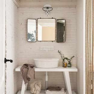 Modelo de aseo romántico, pequeño, con armarios abiertos, puertas de armario blancas, lavabo sobreencimera, paredes blancas, suelo de cemento y suelo gris