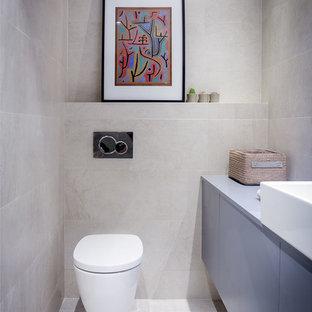 Kleine Moderne Gästetoilette mit grauen Schränken, Wandtoilette, grauen Fliesen, grauer Wandfarbe, flächenbündigen Schrankfronten, Keramikfliesen und Aufsatzwaschbecken in Sonstige