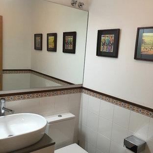 他の地域の小さい北欧スタイルのおしゃれなトイレ・洗面所 (家具調キャビネット、白いキャビネット、一体型トイレ、白いタイル、セラミックタイル、白い壁、無垢フローリング、ベッセル式洗面器、テラゾーの洗面台、茶色い床) の写真