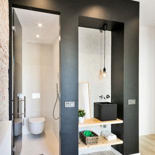 Immagine di un piccolo bagno di servizio industriale con nessun'anta, ante in legno chiaro, WC sospeso, pareti nere, top in legno, lavabo a bacinella, pavimento beige e top beige