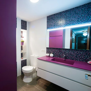Photo of a medium sized contemporary cloakroom in Other with flat-panel cabinets, white cabinets, a two-piece toilet, multi-coloured walls, ceramic flooring, an integrated sink and purple worktops.