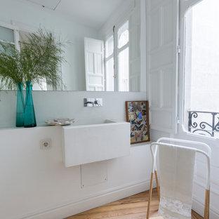 Ejemplo de aseo actual con paredes blancas, suelo de madera clara, lavabo suspendido y suelo beige