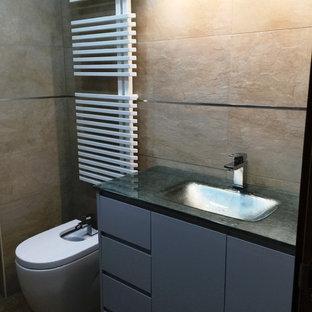 Immagine di un piccolo bagno di servizio moderno con ante lisce, ante grigie, lavabo integrato e bidè
