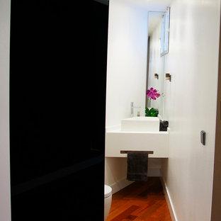 Пример оригинального дизайна: маленький туалет в стиле модернизм с писсуаром, белыми стенами, паркетным полом среднего тона и настольной раковиной