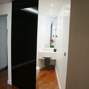 Идея дизайна: маленький туалет в стиле модернизм с писсуаром, белыми стенами, паркетным полом среднего тона и настольной раковиной