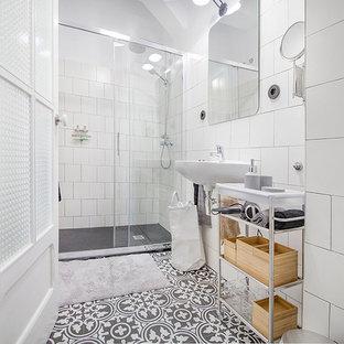 Пример оригинального дизайна: маленький туалет в скандинавском стиле с фасадами островного типа, серыми фасадами, унитазом-моноблоком, белой плиткой, керамической плиткой, белыми стенами, полом из керамогранита, подвесной раковиной и черным полом