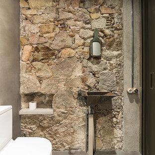 Imagen de aseo industrial, de tamaño medio, con paredes grises, suelo de cemento, lavabo suspendido y sanitario de dos piezas