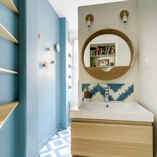 Modelo de aseo escandinavo, pequeño, con armarios con paneles lisos, puertas de armario de madera oscura, baldosas y/o azulejos de cerámica, paredes azules y suelo de baldosas de cerámica