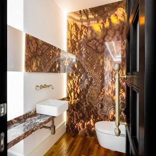 Modelo de aseo clásico renovado, de tamaño medio, con sanitario de pared, baldosas y/o azulejos naranja, baldosas y/o azulejos de mármol, paredes blancas, suelo de madera en tonos medios, lavabo sobreencimera, encimera de ónix y suelo marrón