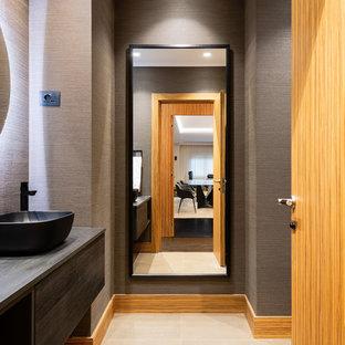 Modelo de aseo actual con armarios con paneles lisos, puertas de armario grises, paredes grises, lavabo sobreencimera, encimera de madera, suelo beige y encimeras grises