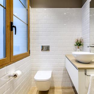 Diseño de aseo contemporáneo, pequeño, con armarios con paneles lisos, puertas de armario blancas, sanitario de pared, baldosas y/o azulejos blancos, baldosas y/o azulejos de cemento, paredes marrones, suelo de baldosas de porcelana, lavabo sobreencimera, suelo marrón y encimeras beige