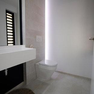 Свежая идея для дизайна: маленький туалет в стиле модернизм с писсуаром, серой плиткой, керамической плиткой, серыми стенами, полом из керамической плитки, монолитной раковиной, столешницей из искусственного камня, серым полом и белой столешницей - отличное фото интерьера