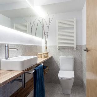 Modelo de aseo contemporáneo, pequeño, con armarios abiertos, baldosas y/o azulejos grises, paredes blancas, lavabo sobreencimera, encimera de madera, suelo gris y encimeras marrones