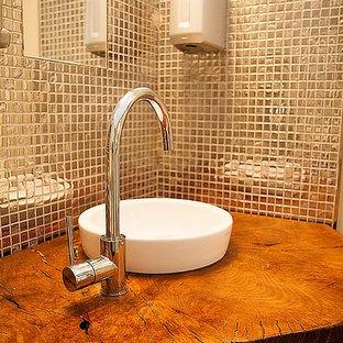 На фото: маленький туалет в стиле модернизм с писсуаром, белой плиткой, керамогранитной плиткой, белыми стенами, полом из керамогранита, настольной раковиной, столешницей из дерева и белым полом с