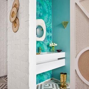 Modelo de aseo actual con suelo con mosaicos de baldosas, suelo gris, armarios con paneles lisos, puertas de armario blancas, paredes azules y lavabo integrado