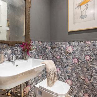 Modelo de aseo tradicional renovado, de tamaño medio, con sanitario de pared, paredes grises, suelo de madera clara y lavabo suspendido