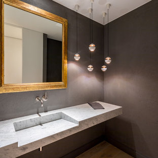 Design ideas for a contemporary cloakroom in Barcelona with black walls, medium hardwood flooring, an integrated sink, marble worktops, beige floors and grey worktops.