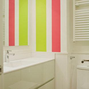 ビルバオの小さいコンテンポラリースタイルのおしゃれなトイレ・洗面所 (フラットパネル扉のキャビネット、白いキャビネット、分離型トイレ、白い壁、一体型シンク、白いタイル、磁器タイル、磁器タイルの床、クオーツストーンの洗面台、白い床、白い洗面カウンター、造り付け洗面台、折り上げ天井、レンガ壁) の写真