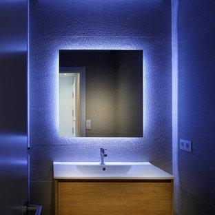 Стильный дизайн: маленький туалет в современном стиле с фасадами островного типа, светлыми деревянными фасадами, инсталляцией, бежевой плиткой, керамогранитной плиткой, бежевыми стенами, полом из ламината, накладной раковиной, столешницей из искусственного кварца и белой столешницей - последний тренд