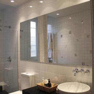 Esempio di un bagno di servizio design di medie dimensioni con WC monopezzo, pistrelle in bianco e nero, piastrelle in ceramica, pareti bianche, pavimento in gres porcellanato, lavabo a bacinella, top in granito e pavimento nero