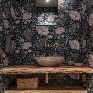 Modelo de aseo romántico, pequeño, con armarios abiertos, puertas de armario beige, paredes beige, suelo de madera en tonos medios, lavabo sobreencimera, encimera de madera, suelo marrón y encimeras marrones
