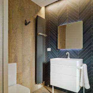 Пример оригинального дизайна: маленький туалет в современном стиле с раздельным унитазом, черной плиткой, черными стенами, паркетным полом среднего тона, коричневым полом, плоскими фасадами, белыми фасадами и консольной раковиной