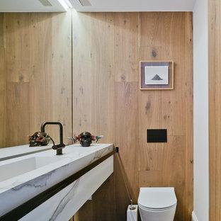 Foto de aseo contemporáneo, pequeño, con sanitario de pared, paredes blancas, suelo de madera en tonos medios, lavabo integrado, encimera de mármol y suelo marrón