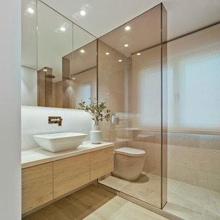 Imagen de aseo actual con armarios con paneles lisos, lavabo sobreencimera, encimeras blancas, puertas de armario de madera clara, sanitario de pared, paredes blancas y suelo beige