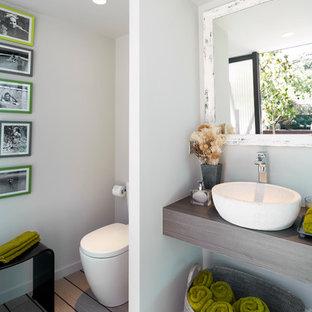Idee per un bagno di servizio contemporaneo di medie dimensioni con WC monopezzo, pareti bianche, parquet chiaro, lavabo a bacinella, top in legno e top marrone