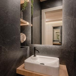 Ejemplo de aseo contemporáneo, pequeño, con puertas de armario de madera clara, baldosas y/o azulejos grises, lavabo sobreencimera y encimeras beige