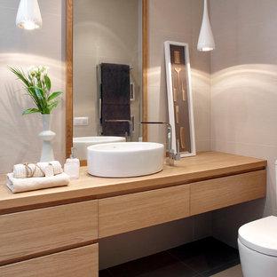 Свежая идея для дизайна: туалет среднего размера в современном стиле с плоскими фасадами, унитазом-моноблоком, серыми стенами, полом из керамической плитки, настольной раковиной, столешницей из дерева, серой плиткой, светлыми деревянными фасадами и коричневой столешницей - отличное фото интерьера