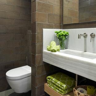 Modelo de aseo actual con armarios abiertos, puertas de armario de madera clara, sanitario de pared, baldosas y/o azulejos marrones, lavabo integrado y suelo gris