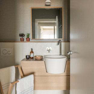 Exemple d'un WC et toilettes bord de mer de taille moyenne avec un placard en trompe-l'oeil, des portes de placard en bois clair, un mur beige, un sol en bois clair, un lavabo posé, un plan de toilette en stratifié, un sol marron et un plan de toilette beige.