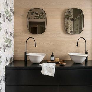 Cette photo montre un WC et toilettes bord de mer de taille moyenne avec des portes de placard noires, un mur multicolore, un sol en bois clair, une vasque, un plan de toilette en stratifié, un sol marron, un plan de toilette noir et un placard à porte plane.