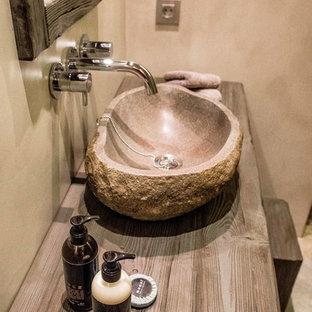 アリカンテの小さいラスティックスタイルのおしゃれなトイレ・洗面所 (グレーのタイル、セメントタイル、グレーの壁、セラミックタイルの床、ベッセル式洗面器、木製洗面台、グレーの床) の写真