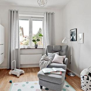 Bild på ett mellanstort skandinaviskt könsneutralt babyrum, med vita väggar, mellanmörkt trägolv och brunt golv