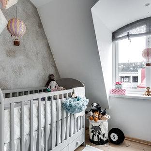 Idéer för ett mellanstort minimalistiskt könsneutralt babyrum, med grå väggar och ljust trägolv