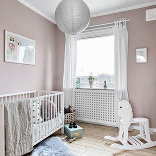 Inredning av ett skandinaviskt babyrum, med rosa väggar, ljust trägolv och beiget golv