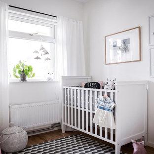 Idéer för ett mellanstort nordiskt babyrum, med vita väggar, mellanmörkt trägolv och brunt golv