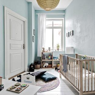 Modelo de habitación de bebé niño escandinava, de tamaño medio, con paredes azules, suelo de madera pintada y suelo blanco