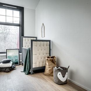 Inredning av ett skandinaviskt mellanstort könsneutralt babyrum, med grå väggar, ljust trägolv och beiget golv