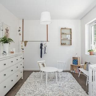 Medium sized scandinavian gender neutral nursery in Stockholm with white walls, dark hardwood flooring and grey floors.