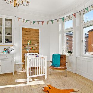 Exempel på ett stort retro könsneutralt babyrum, med vita väggar, ljust trägolv och beiget golv
