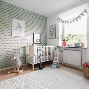 Idéer för ett mellanstort minimalistiskt könsneutralt babyrum, med flerfärgade väggar, mellanmörkt trägolv och brunt golv