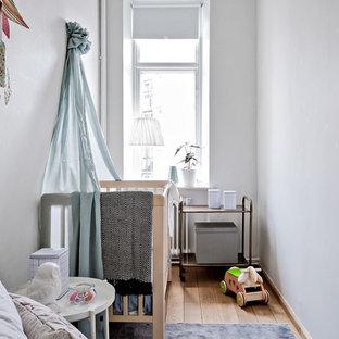 Idéer för små skandinaviska könsneutrala babyrum, med vita väggar, ljust trägolv och beiget golv