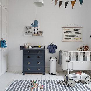 Diseño de habitación de bebé neutra nórdica, de tamaño medio, con paredes blancas, suelo de madera pintada y suelo blanco