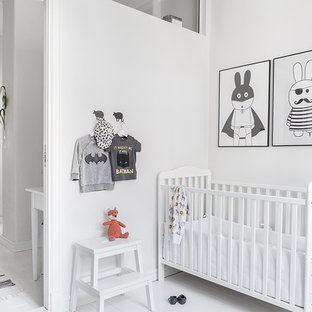 Diseño de habitación de bebé neutra escandinava, de tamaño medio, con paredes blancas, suelo de madera pintada y suelo blanco