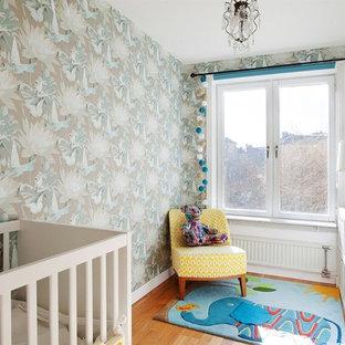Ejemplo de habitación de bebé neutra tradicional renovada, pequeña, con paredes multicolor, suelo de madera clara y suelo naranja