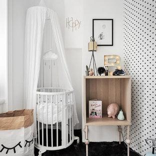 Imagen de habitación de bebé neutra nórdica, de tamaño medio, con paredes negras y moqueta
